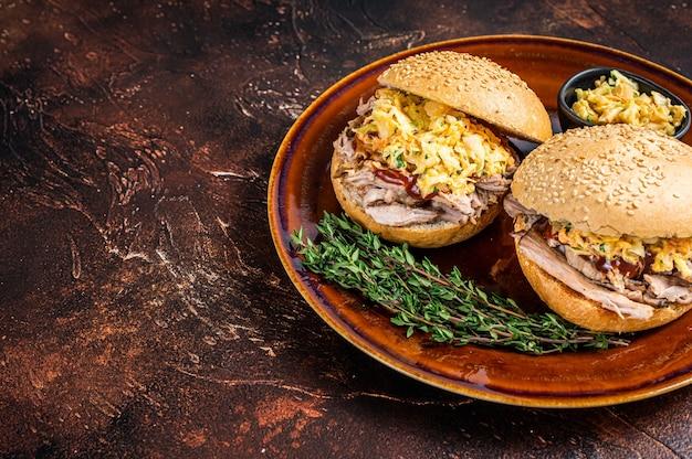코울슬로 샐러드를 곁들인 풀드 돼지고기 햄버거. 어두운 배경입니다. 평면도. 공간을 복사합니다. 프리미엄 사진