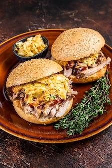 코울슬로 샐러드를 곁들인 풀드 돼지고기 햄버거. 어두운 배경입니다. 평면도.