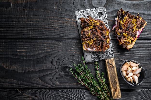 풀드 포크 고기 식칼에 훈제 돼지 고기를 곁들인 샌드위치. 검은 나무 배경. 평면도. 공간을 복사합니다.