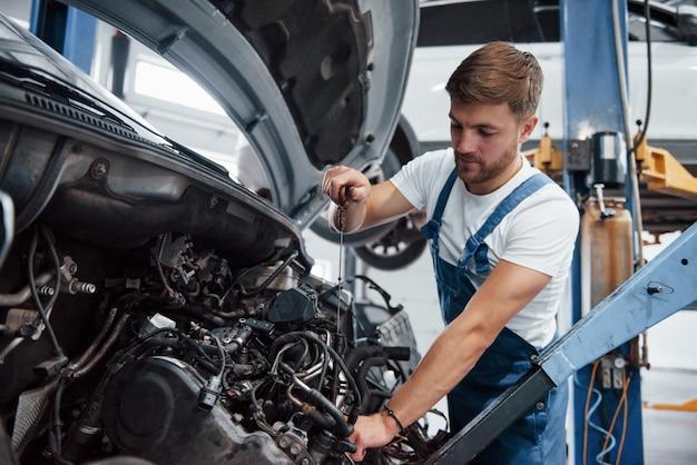 Отрывая металлический трос. сотрудник в синей форме работает в автомобильном салоне