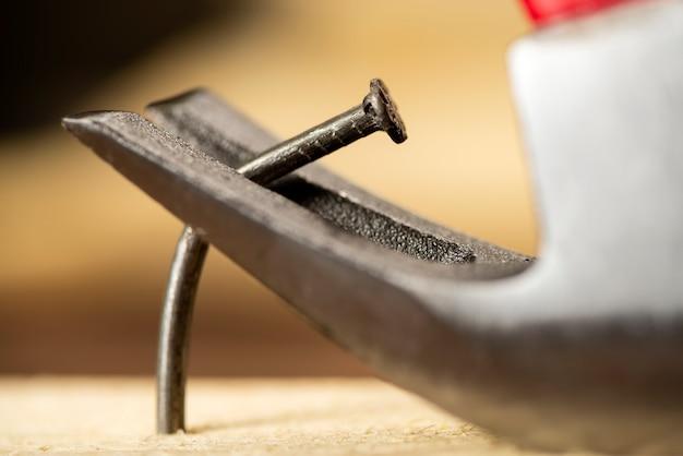 Вытаскивание одного изогнутого гвоздя из деревянной доски молотком