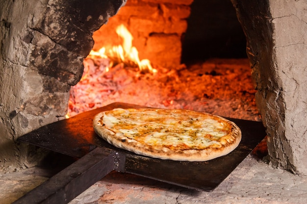パラグアイの手作りオーブン(タタクア)で4チーズのピザを引き出します。