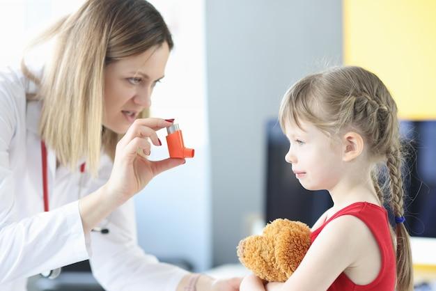 Врач-пульмонолог держит гормональный ингалятор перед лечением бронхов маленькой девочкой