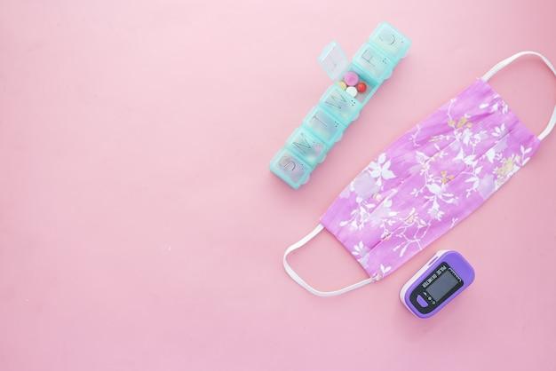 ピンクのパルスオキシメータ布製マスクと医療用錠剤