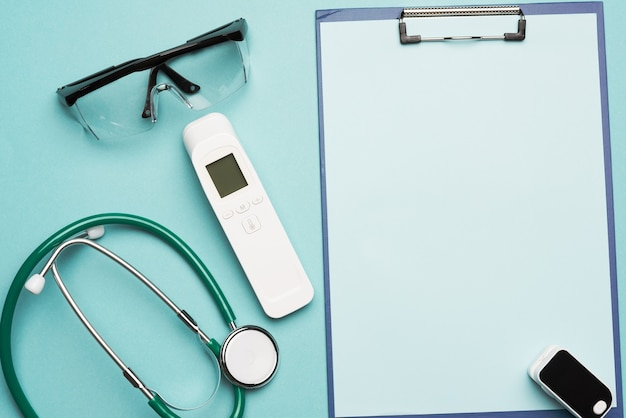 Pulse oximeter and electronic thermometer and other medical supplies on a blue background, copy space