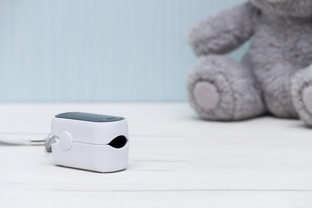 Пульсоксиметр для измерения частоты пульса и уровня кислорода на белом деревянном столе. здоровая концепция.