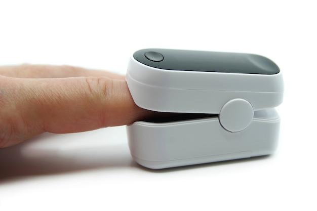 白い背景で分離されたパルスオキシメータ酸素濃度計デバイスの指のクローズアップ