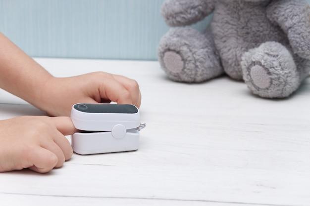 白い木製のテーブルの脈拍数と酸素レベルを測定するための子供の指のパルスオキシメータ。健康的なコンセプト。