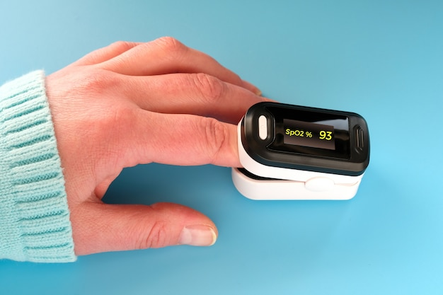 Pulse oximeter portable digital device to measure person's oxygen saturation. reduction in oxygenation is an emergency sign of covid-19 viral pneumonia requiring immediate hospitalization.