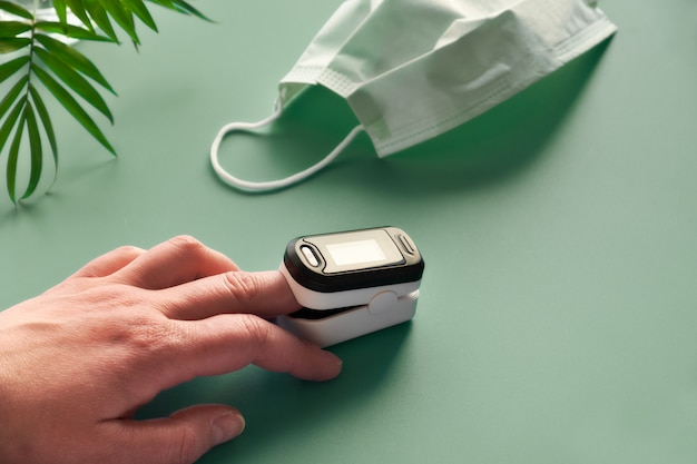 Pulse oximeter portable digital device to measure person's oxygen saturation. reduction in oxygenation is an emergency sign of covid-19 viral pneumonia requiring immediate medical assistance.