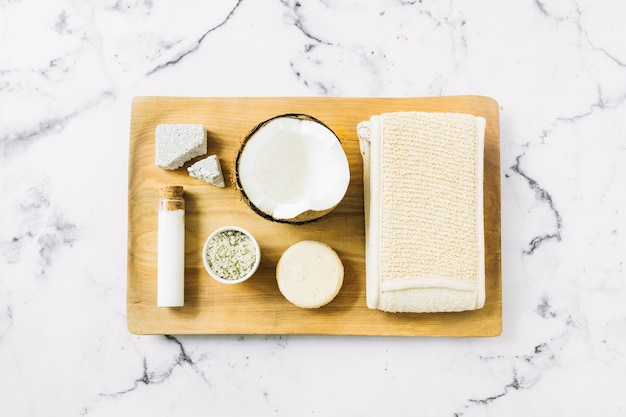 Pumice stone; moisturizer in test tube; halved coconut shell; soap; loofah and scrub on wooden board