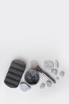 Pumice stone; spa stones; clay mask and brush isolated on white backdrop