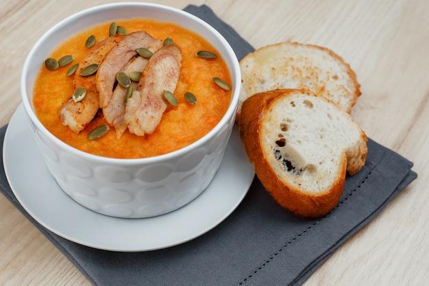 白い皿に七面鳥のpump製とカボチャの種とカボチャのスープ。スープの近くの2つのクルトン。
