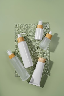 Pump bottle, cream tube, and dropper on green background