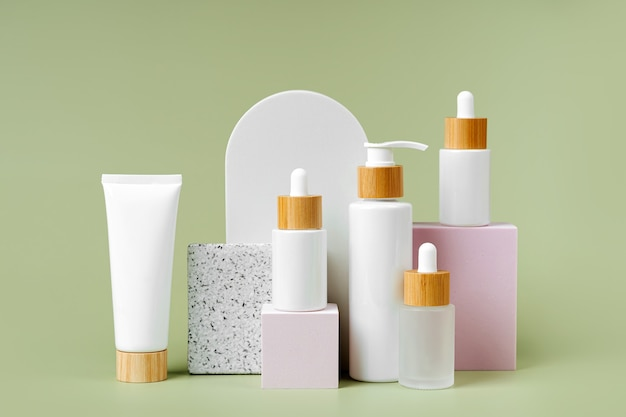 Pump bottle, cream tube, and dropper on square podiums pastel color background