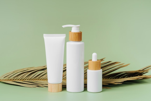 Pump bottle, cream tube, and dropper with palm leaf on green background