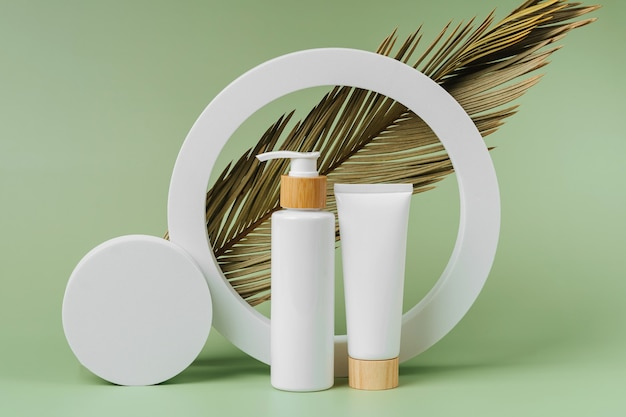 Pump bottle and cream tube with palm leaf on green background