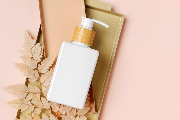 Pump bottle mockup with beige leaf on pastel background