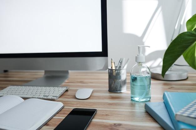 Бутылка с помпой с дезинфицирующим средством для рук на столе человека, рядом с компьютером, планировщиком и смартфоном