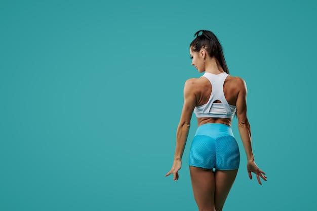 파란색 배경에 카메라에 그녀와 함께 포즈를 취하는 다시 및 팔뚝 근육 강도를 보여주는 피트니스 여자를 펌핑.