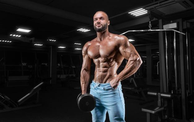 Накаченный мужчина позирует в тренажерном зале в джинсах с гантелью в руке