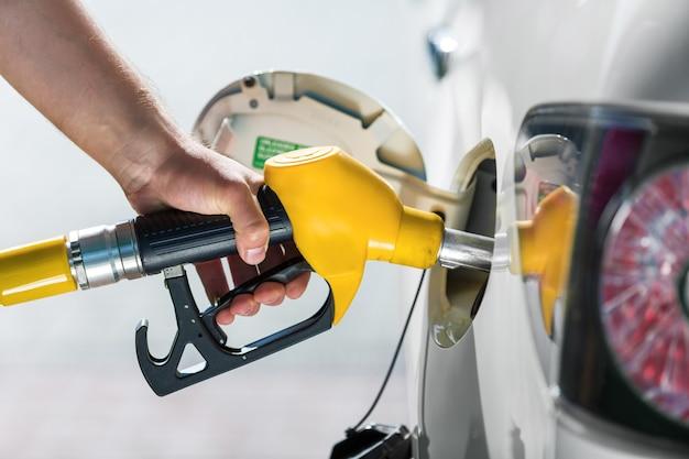 가스 펌프에서 가스를 펌핑합니다. 주유소에서 차에 휘발유 연료를 펌핑하는 남자의 근접 촬영.