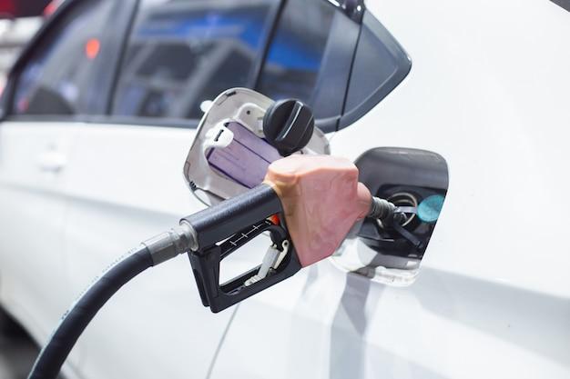 ガソリンスタンドで車のタンクにガソリン燃料ノズルをポンプします。