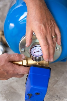 Насосная станция для водоснабжения жилого дома, мастер устанавливает гидроаккумулятор.