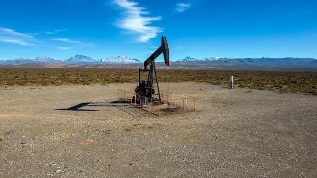 山岳地帯の背景を持つ油を抽出するポンプジャック