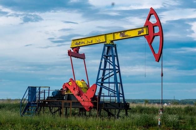 Поршневой насос pumpjack, работающий на нефтяной скважине на открытом воздухе