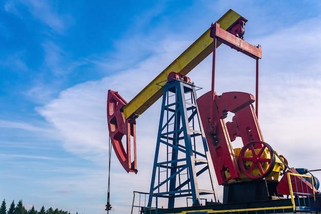 Pumpjack с поршневым насосом на нефтяной скважине на фоне неба