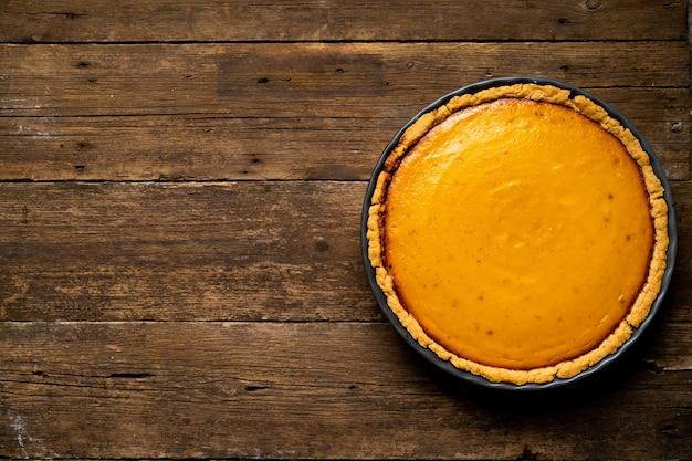 Тыквенный американский пирог на деревянном фоне, вид сверху, копия пространства.