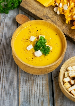 カボチャとニンジンのスープ、ダークウッドのテーブルにクリームとパセリを添えたタッカ。上面図。