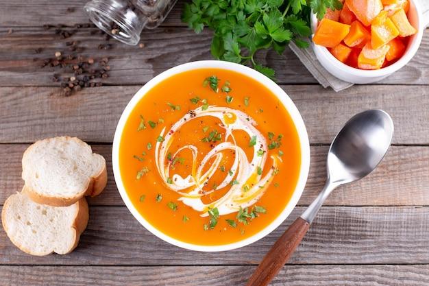 白いプレートにクリームとパセリを添えたカボチャとニンジンのスープ。上面図。ベジタリアンの健康食品の概念。