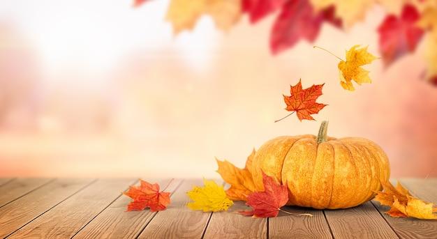Тыква и падающие осенние листья на деревянном столе