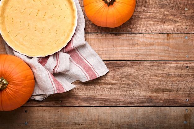 古い素朴な木製の背景にカボチャと食材、スパイス、シナモン、キッチン用品。休日のコンセプト自家製ベーキング。感謝祭の日のためにカボチャのパイとクッキーを調理します。