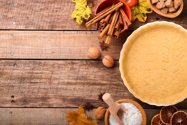 古い素朴な木製の背景にカボチャと食材、スパイス、シナモン、キッチン用品。休日のコンセプト自家製ベーキング。感謝祭の日にカボチャのパイとクッキーを調理します。