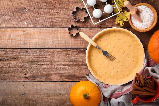 호박과 음식 재료, 향신료, 계피, 주방 기구는 오래된 소박한 나무 배경에 있습니다. 휴가를 위한 개념 수제 베이킹. 추수 감사절을 위한 호박 파이와 쿠키 요리.