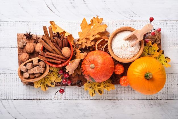 白い素朴な木製の背景にカボチャと食材、スパイス、シナモン、キッチン用品。休日のコンセプト自家製ベーキング。感謝祭の日のためにカボチャのパイとクッキーを調理します。