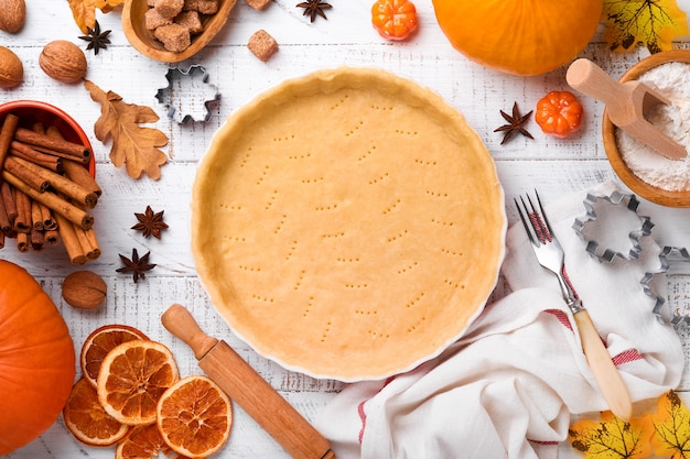 白い素朴な木製の背景にカボチャと食材、スパイス、シナモン、キッチン用品。休日のコンセプト自家製ベーキング。感謝祭の日にカボチャのパイとクッキーを調理します。