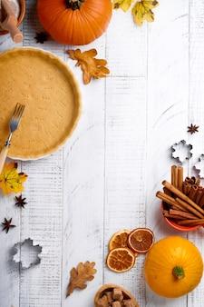 흰색 소박한 나무 배경에 호박과 음식 재료, 향신료, 계피, 주방용품이 있습니다. 휴가를 위한 개념 수제 베이킹. 추수 감사절을 위한 호박 파이와 쿠키 요리.