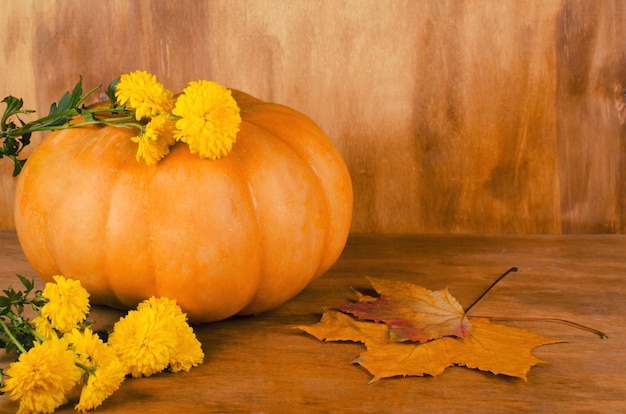 Pumpkin, autumn flowers and leaves on a wooden background