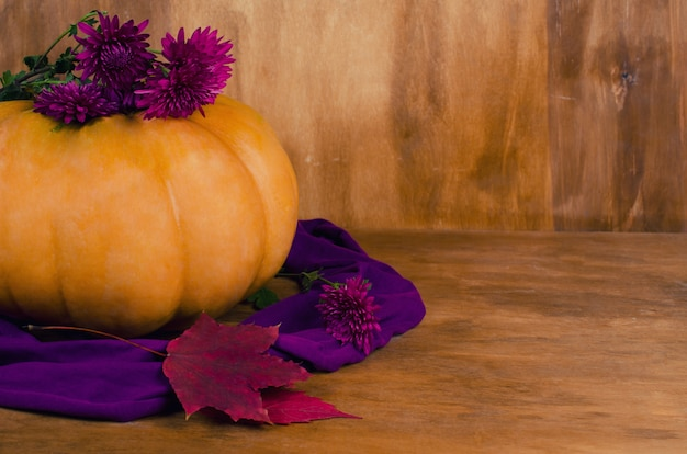 Pumpkin, autumn flowers and leaves