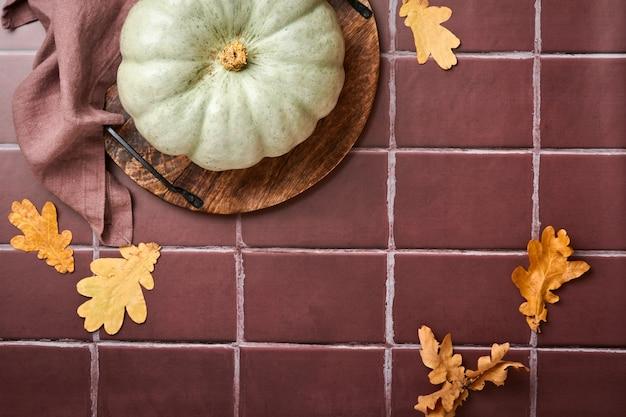 호박. 오래된 세라믹 타일 배경에 계피, 견과류, 계절 향신료가 있는 가을 음식 배경. 추수감사절과 가을 방학을 위해 호박이나 사과 파이와 쿠키를 요리하세요. 평면도.