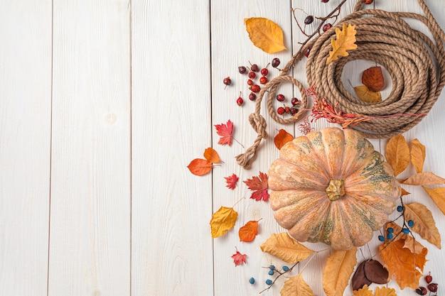 Осенние листья и ягоды тыквы на белом деревянном фоне осенний праздничный фон