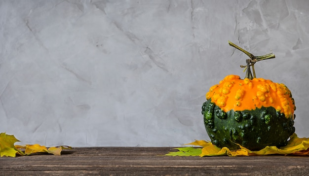 Pumpkin and autumn leaves on wooden table.