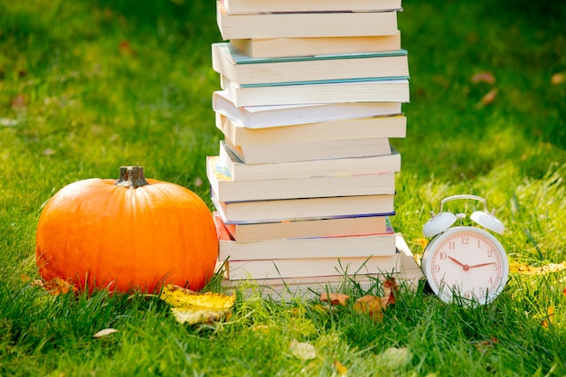 Pumpkin and books with alarm clock are on a green grass in a garden