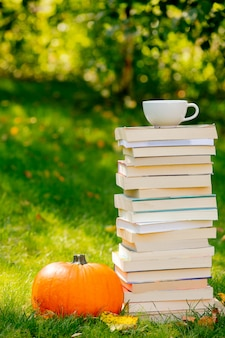 Pumpkin and books with cup of coffee are on a green grass in a garden
