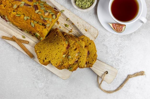 호박 빵, 밝은 회색 표면에 피칸 너트, 호박 씨앗, 계피 향신료와 나무 커팅 보드에 케이크