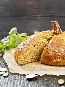 羊皮紙、ニンニク、バジル、黒い木の板の背景に種をカットしたカボチャのパン
